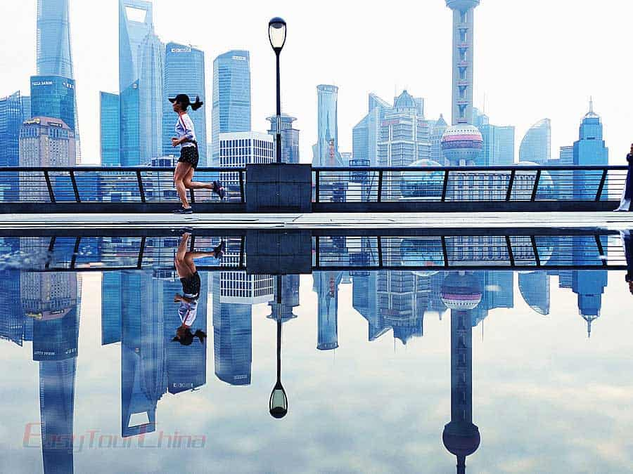 A girl run by Oriental Pearl TV Tower in the morning