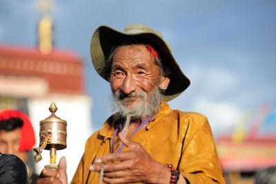 Elderly Tibetan man holding a prayer wheel