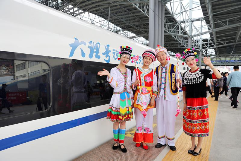 The Local People in Traditional Costumes Poses for a Group Photo by the New Kunming - Dali High-speed Train